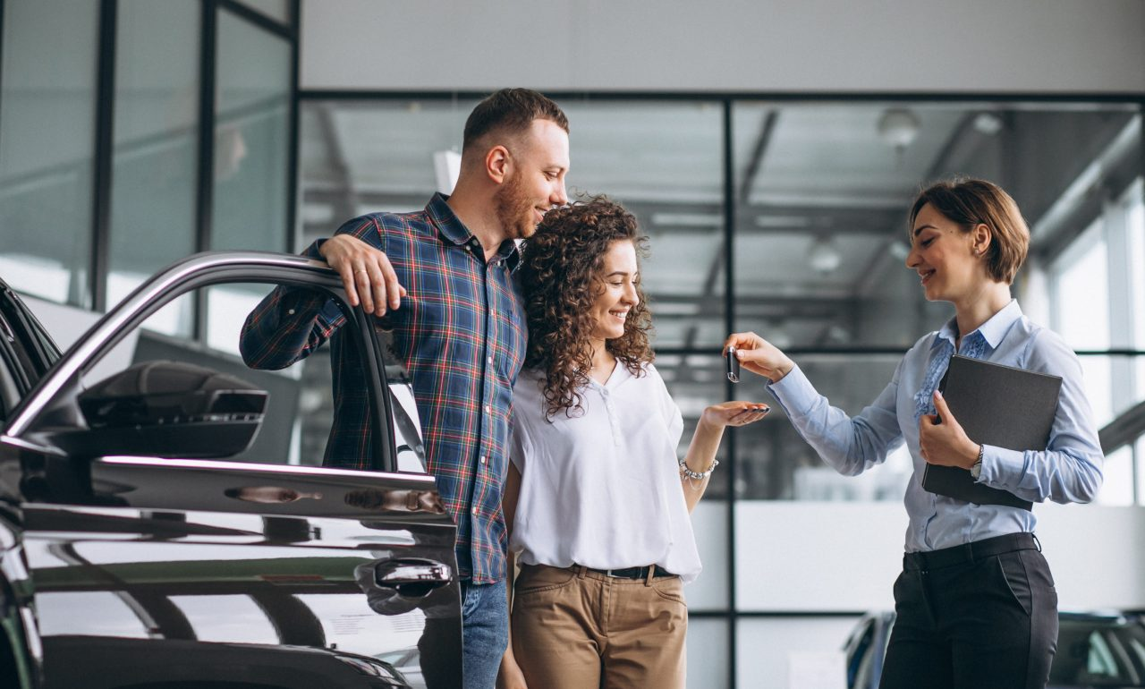 young-couple-choosing-car-car-show-room-scaled.jpg